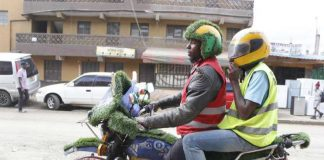 A boda boda operator ferrying a customer.