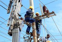 Kenya power workers working on power lines.