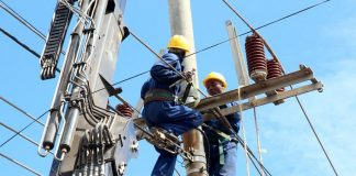 Kenya power workers working on power lines.