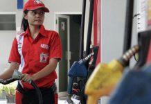 A petrol station attendant fills fuel into a customer's car.