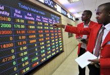 An employee points to stock information displayed on an electronic screen inside the Nairobi Securities Exchange Ltd. (NSE), in Nairobi, Kenya, on Tuesday, Dec. 8, 2015.