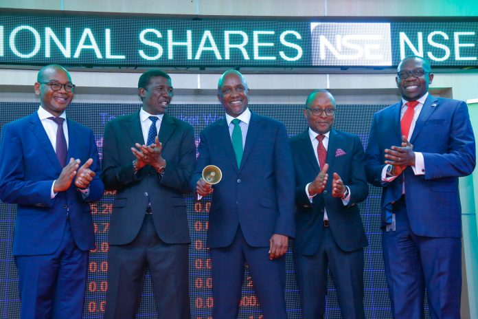 KCB Group Chairman, Andrew Kairu (center) rings the bell after the additional of shares was officially done. He is flanked by Chief Administration Secretary - National Treasury, Nelson Gaichuhie (left), NSE Chairman, Samuel Kimani (right), KCB Group CEO and MD Joshua Oigara (far left) and NSE CEO Geoffrey Odundo (far right) during the additional listing of the NBK shares.