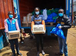SHOFCO Programs Officer Erick Okwam, Jumia Chief Operations Officer Christine Sogomo and a Jumia delivery agent deliver food donations from well-wisher customers at SHOFCO offices in Kibera for needy families