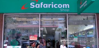 Pedestrians walk past a Safaricom shop in Nairobi on November 22, 2018.