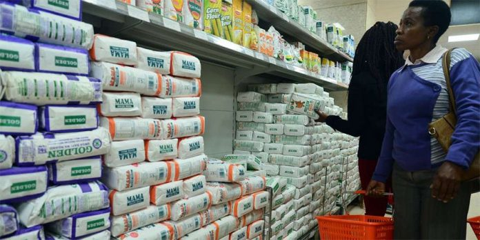 A female customer inspects different brands of maize meal at a local supermarket.