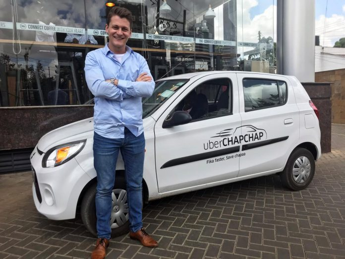 Uber's East Africa general manager Loic Amado poses for a picture near a vehicle of Uber operating taxi at a parking lot in Nairobi
