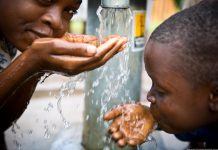 Children drinking water from a tap. Water pollution will affect water sustainability