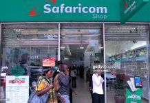Pedestrians walk past a Safaricom shop in Nairobi on November 22, 2018.